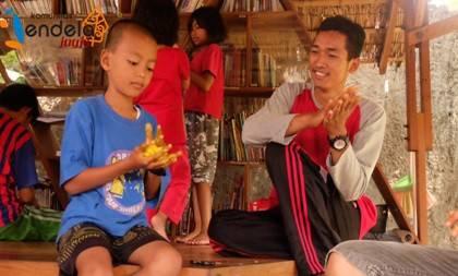 Seorang anak meratakan pewarna kuning ke adonan slime-nya .