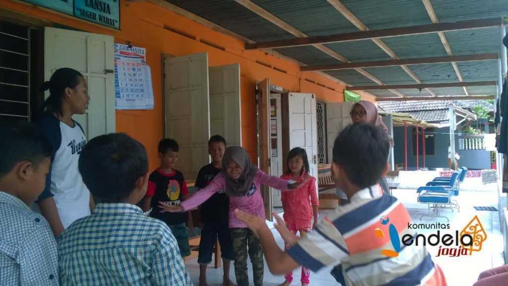 Bermain tebak gerak-gerik : Seorang anak sedang meragakan suatu aktivitas untuk ditebak teman-temannya.